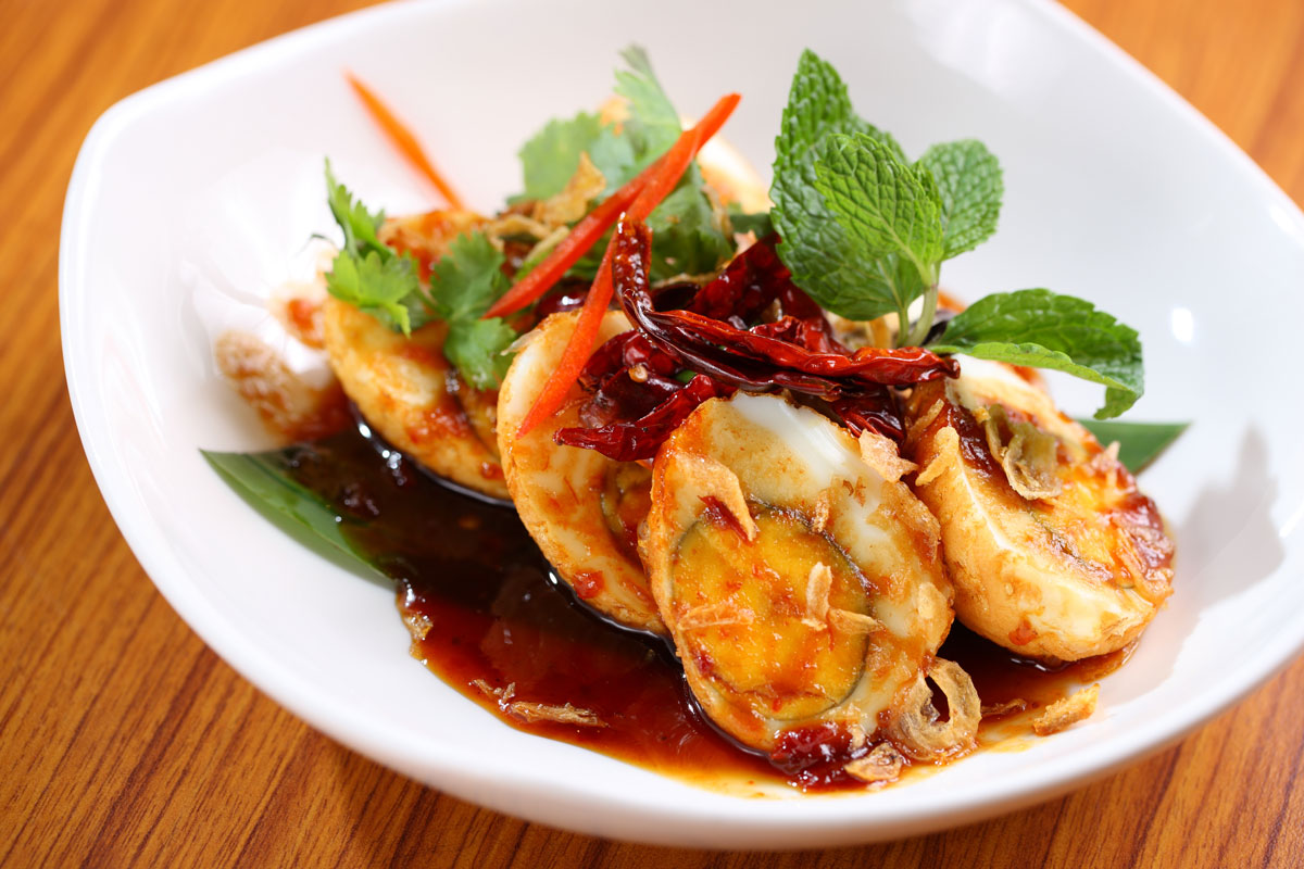Lotus_Son-in-law-eggs-with-tamarind-sauce,-coriandar-and-crispy-shallots-sized